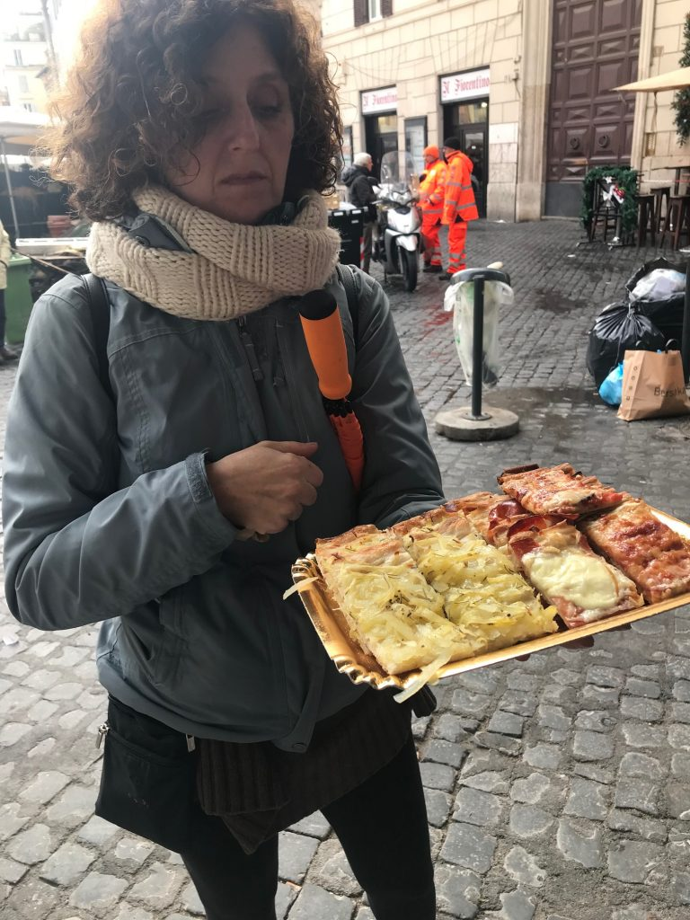 Silvia , guide from Secret Food Tour serving us fresh pizza